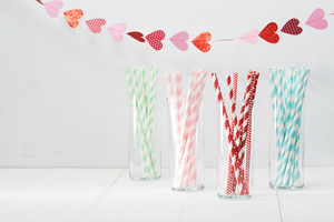 Colorful paper straws with a decorative garland of hearts symbolic of love to celebrate a party for a festive romantic occasion, with copyspace for your invitation or greeting