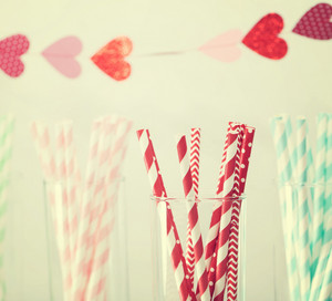 Colorful paper straws with a decorative garland of hearts symbolic of love to celebrate a party for a festive romantic occasion