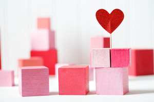Colorful red and pink wooden blocks with small heart on white background