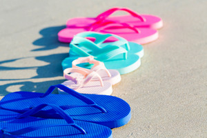 Colorful sandals on the sand at the beach