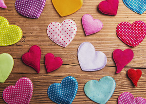 Colorful textile hearts on the floor. Studio shot on wooden background.