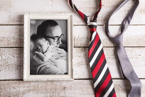 Colorful tie and picture of young father holding his cute newborn baby son in the arms. Fathers day concept. Studio shot on white woden background.