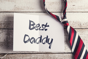 Colorful tie and piece of paper with Best daddy sign. Fathers day concept. Studio shot on woden background.