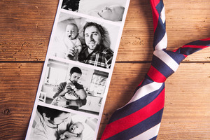 Colorful tie and various pictures of young father and his cute newborn baby son. Fathers day concept. Studio shot on woden background.