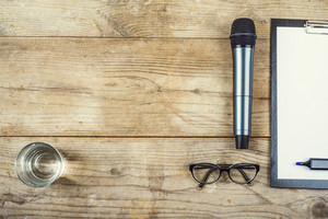 Composition of office gadgets and supplies on a wooden desk background. View from above.