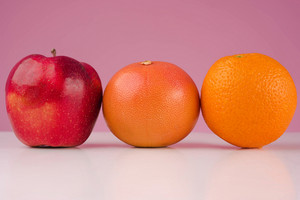 Composition with fruits apple, grapefruit and orange isolated on a pink background