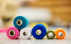 Composition with spool of colorful tailor threads laid on table