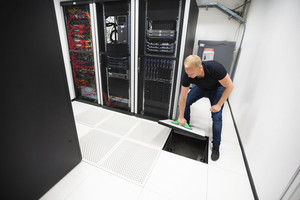 Computer Engineer Lifting Floor Tile Using Suction Cups In Datac
