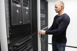 Computer Engineer Opening Server Rack Door In Data Center