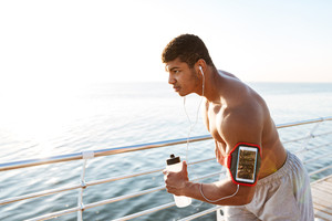 Concentrated african american young man athlete with blank screen smartphone in armband working out and drinking water