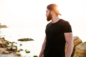 Concentrated bearded sports man standing at the beach and looking at sunset