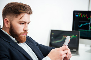 Concentrated bearded young businessman working and using cell phone in office