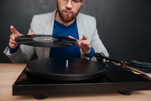 Concentrated bearded young man in glasses using turntable and vinyl record
