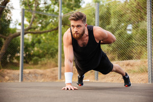 Concentrated bearded young sportsman doing push-ups with one hand outdoors