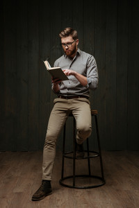 Concentrated handsome young bearded man in eyeglasses sitting and reading a book isolated on a black wooden background