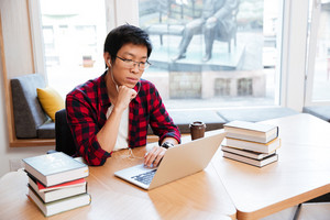 Concentrated man dressed in shirt in a cage and wearing glasses using laptop at the library and listen to music. Looking at laptop.