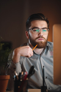 Concentrated web designer dressed in shirt and wearing eyeglasses working late at night and looking at computer. Holding pencil.