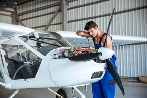 Concentrated young aircraftsman repairing small aircraft