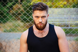 Concentrated young bearded man in tshirt looking at camera outdoors