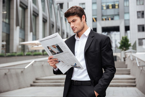 Concentrated young businessman standing and reading newspaper outdoors