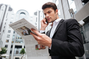 Concentrated young businessman talking on cell phone and reading newspaper near business center