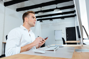 Concentrated young businessman using computer and mobile phone at workplace