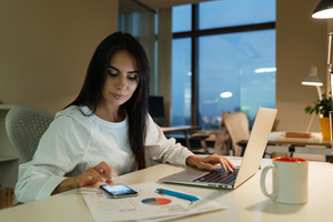 Concentrated young businesswoman using mobile phone and working with laptop in office