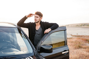 Concentrated young casual man standing at his car parked on the seaside