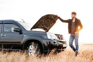 Concentrated young man holding hands on vehicle hood and looking inside it while standing outdoors
