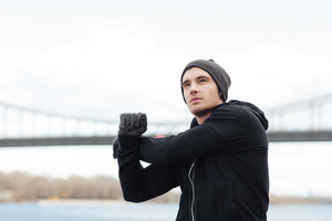 Concentrated young man in hat and gloves doing exercises outdoors
