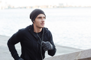 Concentrated young man with earphones running outdoors