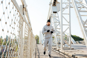 Concentrated young sports man jogging across bridge outdoors
