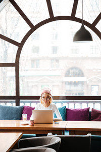 Concentrated young woman in hat and glasses working with laptop in cafe