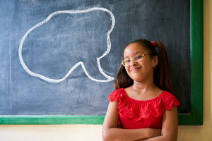Concept on blackboard at school. Happy and funny latina girl in class, leaning on blackboard. Portrait of female child looking at camera with drawing of cloud in background