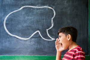 Concept on blackboard at school. Young people, student and pupil in classroom. Hispanic boy screaming in class with drawing of cloud on blackboard. Portrait of frustrated male child
