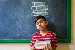 Concept on blackboard at school. Young people, student and pupil in classroom. Sad and bored hispanic boy in class. Portrait of male child looking at camera, holding books