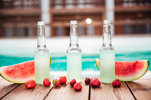 Concept photo alcohol bottles with fresh strawberries and halves of watermelon with pool on the background