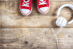 Concept with red sneakers and white headphones laid on wooden floor background.