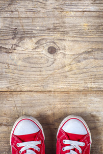Concept with red sneakers laid on wooden floor background.