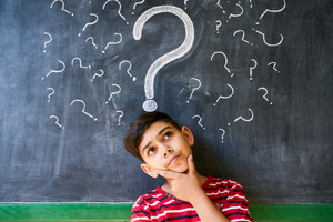 Concepts on blackboard at school. Hispanic boy with doubts and thoughts in class. Portrait of male child thinking against question marks on blackboard