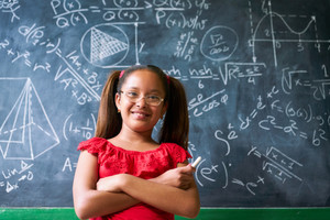 Concepts on blackboard at school. Young people, students and pupils in classroom. Smart hispanic girl writing math formula on board during lesson. Portrait of female child smiling, looking at camera
