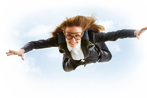 Conceptual image of young female flying with parachute on her back