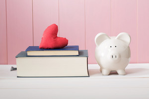 Conceptual White Ceramic Piggy Bank Standing Beside Textbooks with Red Heart Cushion on Top Against Wooden Pink Wall