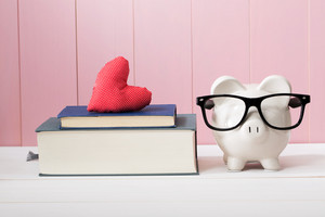 Conceptual White Piggy Bank with Eyeglasses Standing Beside Textbooks with Small Red Heart Cushion Against Wooden Pink Wall.