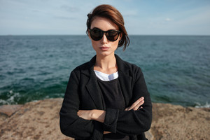 Confident attractive young woman in sunglasses standing with arms crossed on seashore