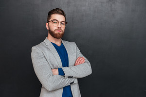 Confident bearded young businessman standing with arms crossed