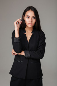 Confident business woman standing in black suit over gray background