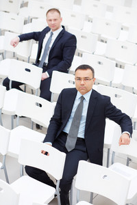 Confident businessmen sitting on chairs of conference hall