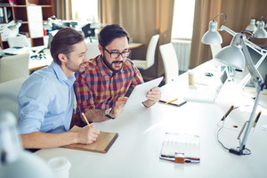 Confident businessmen studying data and making notes at meeting