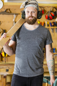 Confident craftsman with safety mask and earmuffs in workshop